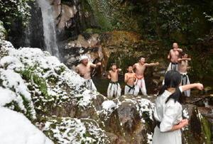滝つぼに入り、かけ声と共に突きを繰り出す「清風會」の門下生たち=鳥栖市立石町の御手洗の滝