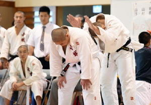 柔道男子団体 試合に臨む選手の背中をたたき、気合を入れる=基山町総合体育館