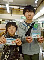 一番乗りで漫☆画太郎さんデザインのカードを手にした武藤淳平さん(右)=佐賀県立図書館