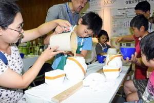 型を使った有田焼のマグカップ作りを体験する来場者=佐賀市の市村記念体育館
