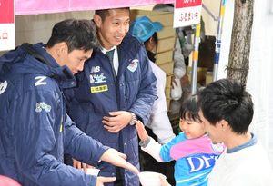 サポーターに豚汁を配る(左から)趙東建選手と金敏爀選手=鳥栖市民文化会館