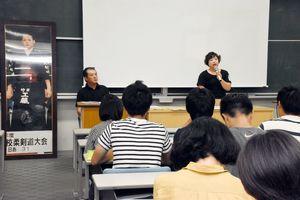 剣太さんの等身大写真パネルの横で学生に語る工藤奈美さん(右)、英士さん=佐賀市の佐賀大学本庄キャンパス