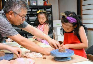 手ほどきを受けながら湯飲み作りに取り組む池田さん姉妹=鳥栖市山浦町の陶芸工房「然」