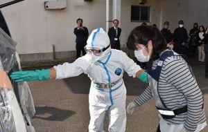 新型インフルエンザ対応訓練で、患者役の女性(右)を病院に搬送するため誘導する職員=伊万里市の伊万里保健福祉事務所