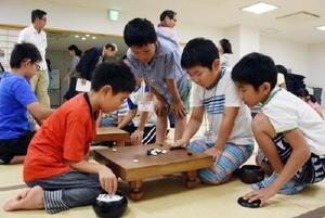 真剣な表情で碁を打つ子どもたち=鹿島市の市民交流プラザ「かたらい」