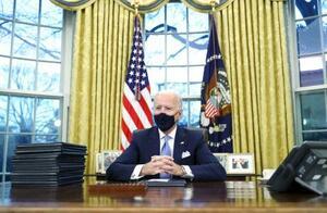 米ホワイトハウスの執務室で大統領令に署名したバイデン大統領=20日、ワシントン(ロイター=共同)