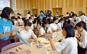 交流会で、佐賀県内の高校生の説明を受けながらようじ入れを作る参加者=小城市のゆめぷらっと小城