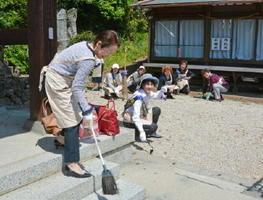 須賀神社の社務所の敷地を清掃する国際ソロプチミスト佐賀中部のメンバーら=小城市小城町の須賀神社