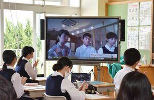 教室の電子黒板に映る生徒会役員や議長の顔を見ながら、説明に耳を傾ける生徒たち=小城市の小城中