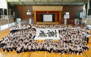 現校舎への感謝を込めた寄せ書きと記念撮影する生徒たち=神埼市の神埼高