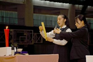 中島ヤスの功績をしのび、句を詠み上げた佐賀女子高3年の河野杏さん(左)=佐賀市本庄町の旭学園体育館