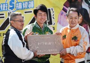 「スカジャン」発祥の地を宣言するイベントで、記念プレートを手に写真に納まる自民党の小泉進次郎筆頭副幹事長(中央)。右は横須賀市の上地克明市長=12日、神奈川県横須賀市