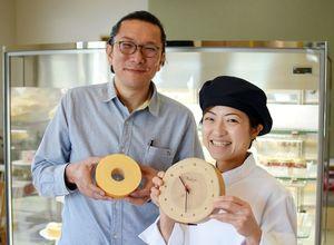 年輪時計を手にする古林茜さん(右)とバウムクーヘンを持つ實松英樹さん=佐賀市大和町