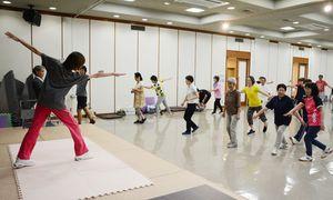 講師の指導を受けてリズムダンスに挑戦する参加者たち=佐賀新聞社