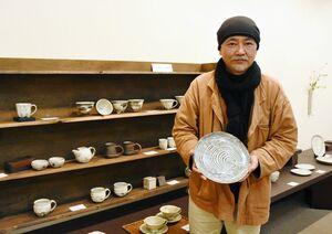 粉引の「年輪プレート」を持つ吉田求さん。約200点の器を並べる=佐賀市の高伝寺前村岡屋ギャラリー