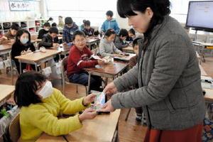 「ブラックモンブラン」形のメモパッドを受け取る児童=佐賀市の循誘小学校
