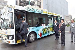 完成したラッピングバスに乗り込む技術者ら=佐賀市役所