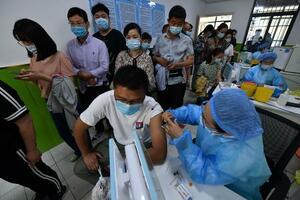 中国安徽省で新型コロナウイルスのワクチンを投与する医療従事者(右)=5月29日(ゲッティ=共同)