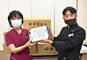 伊万里有田共立病院に弁当を差し入れたステーキハウス店長の立川雄二郎さん(右)と宮地千加子看護部長=有田町の同病院