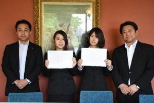 県生命保険協会の脇田純一副会長(右)から通知書を受け取った、冨田梨奈さん(左から2人目)と服巻春香さん(同3人目)=佐賀市のホテルニューオータニ佐賀