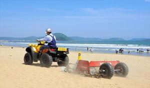 ビーチクリーナー(後部)で砂に埋まったごみを回収するホンダ関係者=唐津市東の浜