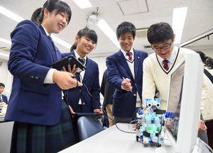 プログラミングしたロボットの動きに笑顔がこぼれる生徒たち=佐賀市の致遠館高