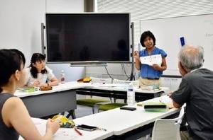 リスニングでどのようなことを話しているかを聞き取って確認する受講生=佐賀市の県国際交流プラザ