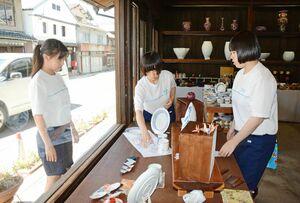 通りからの見え具合を確認しながら焼き物などを配置する牛津高の生徒たち=有田町幸平の手塚商店