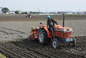 麦まき作業の遅れを取り戻そうと急ピッチで作業を進める生産者。あちこちの圃場でトラクターが忙しく動き回っている=佐賀市川副町
