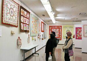 一針一針、思いが込められた作品を鑑賞する人たち=佐賀市城内の県立美術館