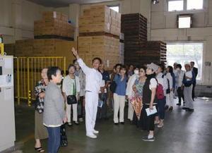 箱詰めされた商品が並ぶ工場内を見学するバスハイク参加者=唐津市船宮町の宮島醤油