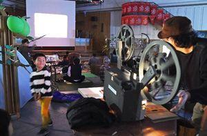 森に見立てた会場で16ミリフィルムを映し出した野外上映会=佐賀市の656広場