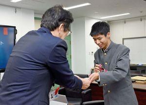 準優勝のメダルを見せ、はにかむ板橋直哉さん=佐賀県庁