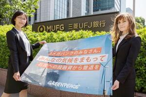 石炭火力発電への融資をやめるよう金融機関に求める横断幕を掲げるグリーンピースのメンバー=2018年5月、東京都千代田区(グリーンピース提供)