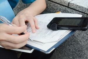 曳山展示場でスマホを使って調べ物をしてメモを取る高校生の手元