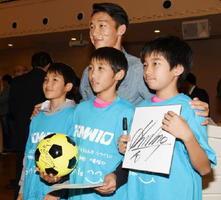 記念Tシャツを着て金民友選手と写真に収まる子どもたち=佐賀市の「アルカディアSAGA」