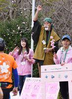 「花咲かじいさん」にふんし、紙の花びらをまく佐賀大学の学生=佐賀市の多布施川沿い