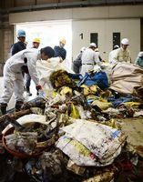 玄海町で回収したごみを分別する作業員ら=唐津市北波多の市清掃センター