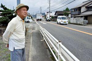 太平洋戦争末期、旧日本軍の滑走路があった国道203号を見つめる中山作馬さん=小城市小城町畑田