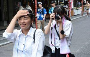 祐徳稲荷神社門前の商店街で狐のお面をかぶり、撮影を試みる生徒たち=29日、鹿島市