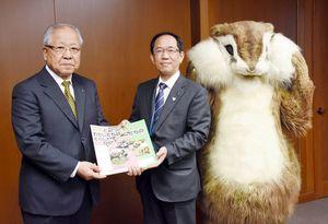 教材本を手渡した川﨑裕之常務理事(右)と杉﨑士郎会長=佐賀市の県庁
