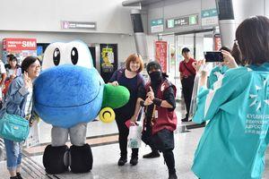 佐賀空港のマスコットキャラクター「むっぴー」や佐賀忍者と記念撮影する観光客=佐賀市の佐賀空港