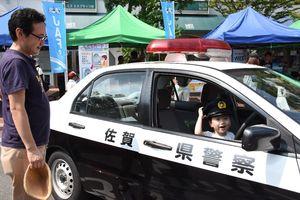 乗車体験でパトカーに乗る子ども=佐賀市のエスプラッツ