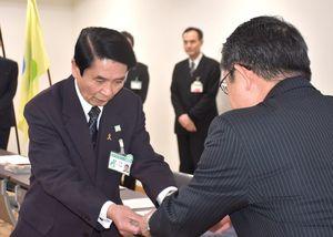 「佐野常民伝」などを手渡す船津事務局長と受け取る東島教育長(左)=佐賀市役所