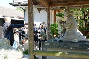 百婆仙の像を前に説明を受けるSNSサポーターズら=有田町岩谷川内のギャラリーペクパソン