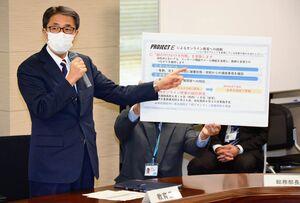 佐賀県立高校の生徒が持つタブレット端末を生かし、健康状態や課題の進ちょくなどに活用する取り組みを説明する落合裕二教育長=県庁