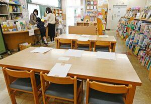 感染症対策を強化し、開館している佐賀県立図書館。机に張り紙をして利用者同士の間隔を空ける工夫や、扉や窓を開放して換気に努めている=18日午前、佐賀市城内(撮影・米倉義房)