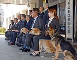 嘱託を受けた警察犬と指導手ら関係者=佐賀市の県警本部