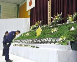 慰霊碑に献花し、一礼する警察官ら=佐賀市の県警察学校