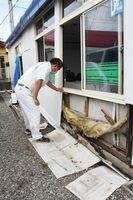 冠水した国道34号を走行した大型トラックが波を立て、事務所のガラスや壁を壊したとみられる「ニシイ」の事務所=武雄市北方町志久